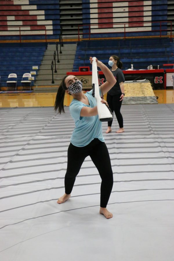 Junior Mackenzie Taylor works on a skill for the beginning of the winter guard's show. The group has a competition tomorrow.